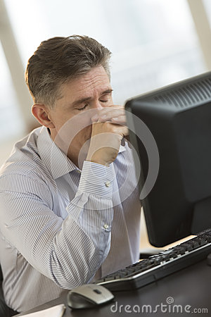 Exhausted Businessman Leaning On Computer Desk