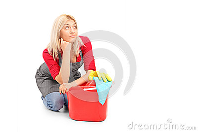 Exhausted female cleaner sitting next to a bucket