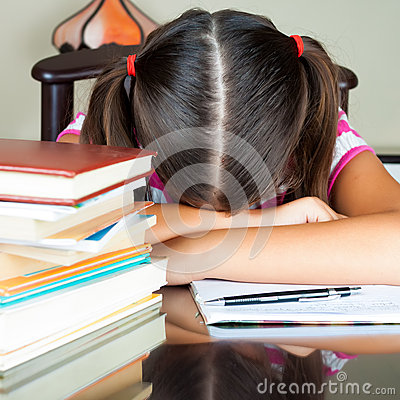 Exhausted girl sleeping on her desk