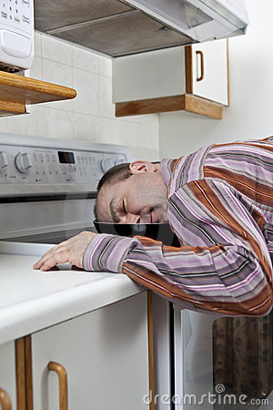 Exhausted man asleep in a frying pan