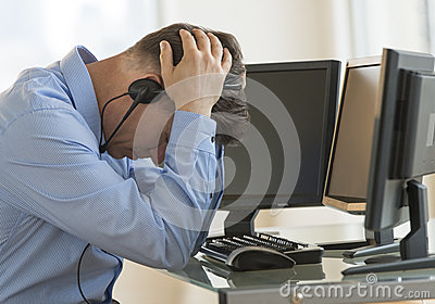 Exhausted Trader With Head In Hands Leaning At Computer Desk