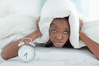 Exhausted woman covering her ears with a duvet