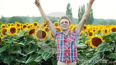 Exitoso agricultor muy feliz de la victoria y rica cosecha en el campo de los girasoles, complacido y positivo al atardecer almacen de video