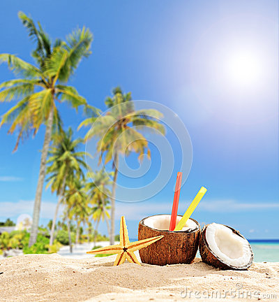 Exotic cocktail in coconut cup on tropical beach