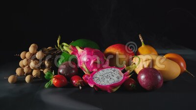 Exotic fruits in the white smoke. Video of exotic fruits with smoke on black background stock video