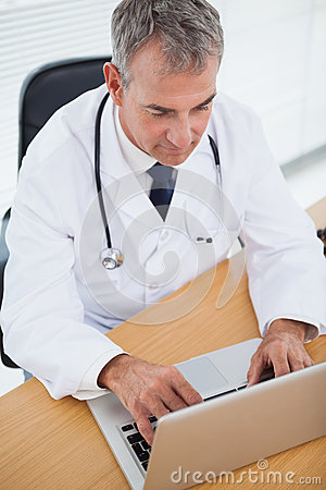 Experienced doctor typing on his laptop