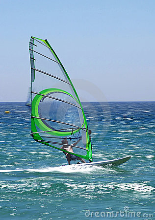 Experienced windsurfer speeding along sunny blue sea giving a real feeling of motion.