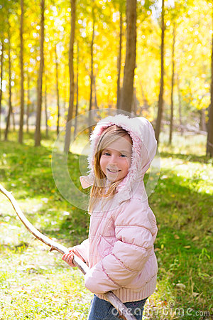 Explorer girl with stick in poplar yellow autumn forest
