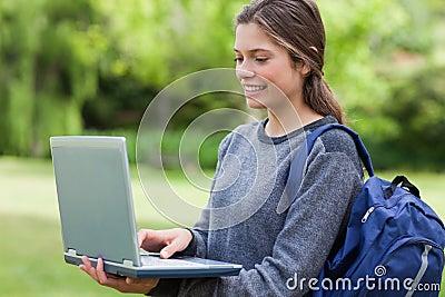 Explotación agrícola sonriente joven de la mujer su computadora portátil