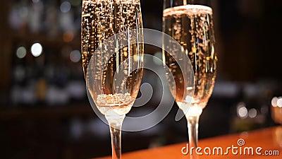 Exponeringsglas med champagne med bubblor som stiger upp på unfocused bakgrund lager videofilmer