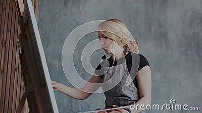 Exprese su creatividad Dibujo positivo de la mujer joven en el caballete mientras que disfruta de su afición Se aplica la pintura almacen de video