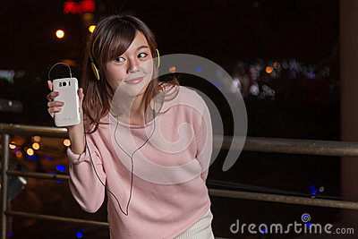 Expressive Asian woman with smart phone and yellow headphones