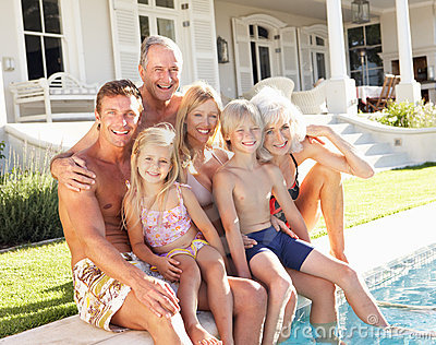 Extended Family Outside Relaxing By Swimming Pool