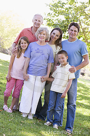Extended family standing in park holding hands
