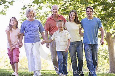 Extended family walking in park holding hands