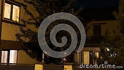 Exterior de uma casa esperta europeia amarela da vizinhança residencial que está sendo iluminada automaticamente em cada sala - video estoque
