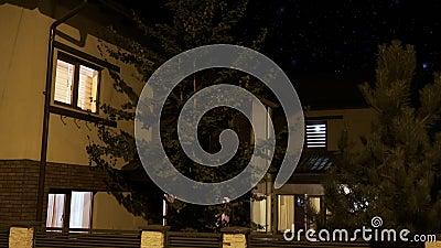 Exterior de uma casa esperta iluminada gradualmente em cada sala em uma vizinhança residencial na noite - video estoque