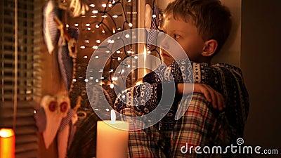 Extrémité du petit garçon triste de Noël s'asseyant sur le rebord de fenêtre clips vidéos