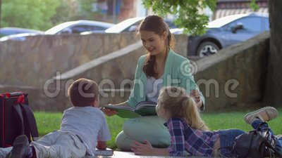 Extracurricular activities, cute kids listening to woman reading book after  school sitting on green grass in nature in