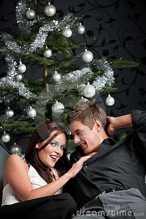 Extravagant couple in front of Christmas tree