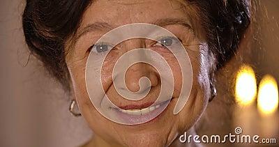 Extrema cara de cara de brunette caucásica madura con ojos marrones mirando la cámara y sonriendo Retrato de lo antiguo almacen de video