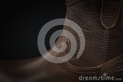 Extreme close-up of a brown leather cowboy boot on black