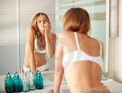Eye care - Young woman checking her dark circles