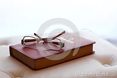 Eyeglasses on Holy Bible with backlighting