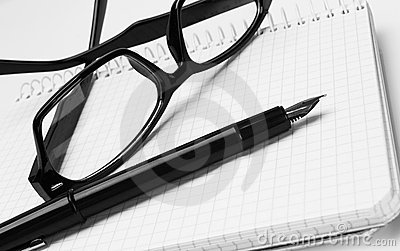 Eyeglasses and pen, on notepad