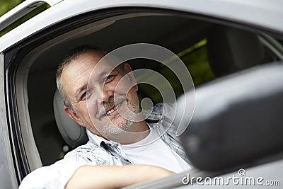 Fälliger Kraftfahrer, der aus Auto-Fenster heraus schaut