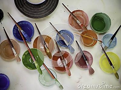 Färgrikt måla cans och borstar i atelier