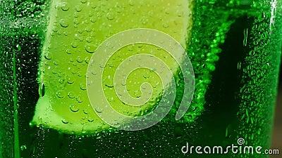 Färsk juicedel av grönt kalk på botten av ett glas med en grön cocktail lager videofilmer