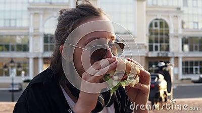 A fêmea nova come um Hamburger grande, suculento com duas mãos Moça com cabelo curto e os óculos de sol escuros hungry fim vídeos de arquivo