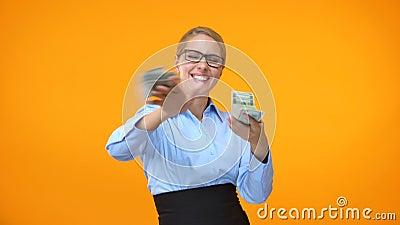 Fêmea positiva em dólares de jogo do terno formal ao redor, independência financeira video estoque