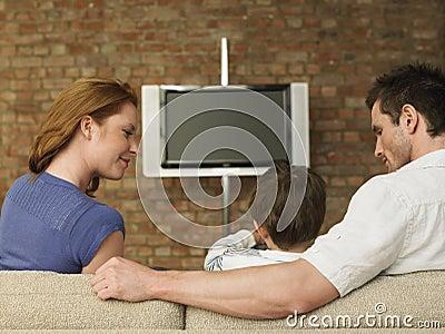 Föräldrar som hemma ser hållande ögonen på TV för pojke