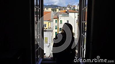 För öppningsfönster för ung kvinna stad för morgon italiensk medeltida lager videofilmer