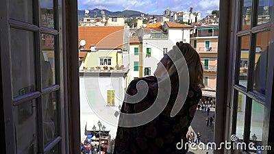 För öppningsfönster för ung kvinna stad för morgon italiensk medeltida arkivfilmer