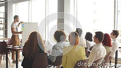 Företagsanställda samlade på konferenssalen och tittade på produktpresentation och anteckningar arkivfilmer