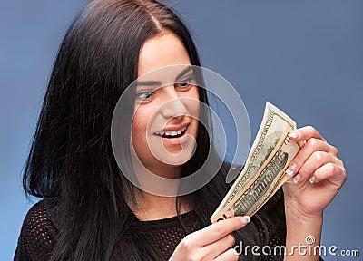 Förvånad kvinna med dollarräkningar