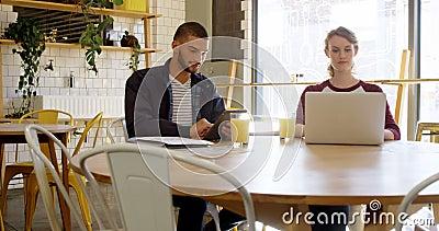Führungskräfte, die an digitaler Tablette und Laptop in der Cafeteria 4K 4k arbeiten stock footage