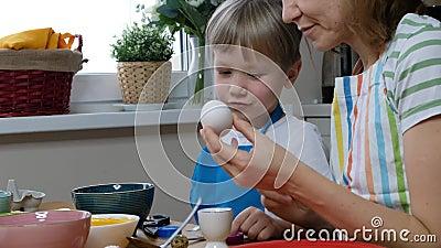 Fünf Jahre alter Junge, der Ostereier mit Eizellfarbstoff färbt stock video footage