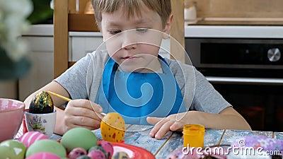 Fünf Jahre alter Kleinkind, der Ostereier in der Küche färbt stock video