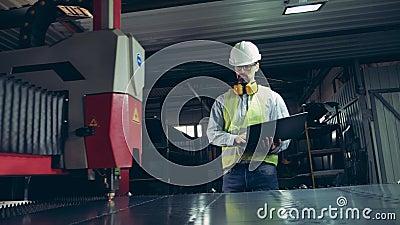 Fabrieksmedewerker kijkt naar laserapparatuur die metaal snijdt Professionele zware technicus stock video