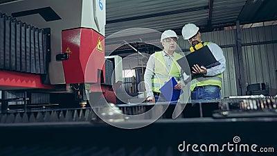 Fabrieksmedewerkers onderzoeken een lasermachine die metaal snijdt stock videobeelden