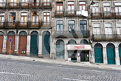 Facade of the lower stories of an apartment house on a steeply sloped cobblestone street in Porto, Portugal Editorial Stock Photo