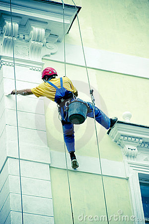 Facade painter on abseil ropes