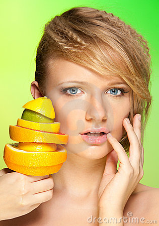 Face of beautiful woman with pyramid of fruits