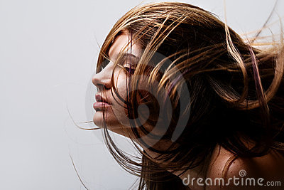 Face of beautiful young woman with hair flying