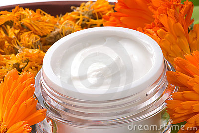 Face cream and calendula flowers