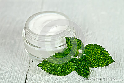 Face cream in glass jar with green leaf of urtica Stock Photo